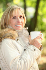 mature woman having coffee outdoors