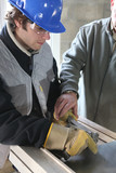 Apprentice learning how to cut sheet metal