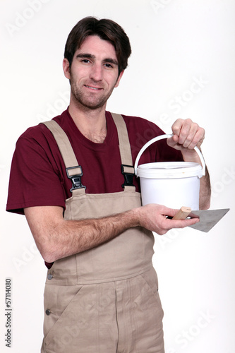 Man with a pot of grout