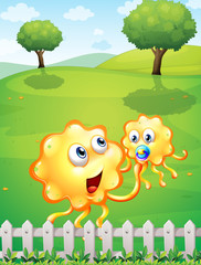 A hilltop with an orange monster playing with a baby monster