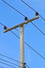 Electricity lines and post under blue sky