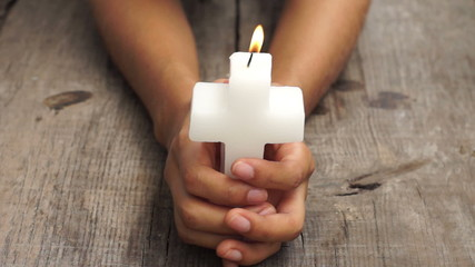A person holding a lit crucifix candle on wood background