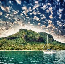 Polynésie. Île et de la végétation au coucher du soleil avec petit bateau sur fo