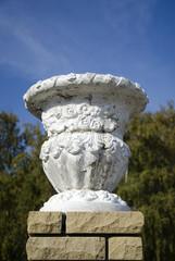Old plaster garden vase on a modern brick pedestal on tree backg