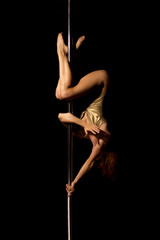 Sexy young female pole dancer on black background