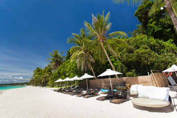 Sun umbrellas and beach chairs on tropical coast