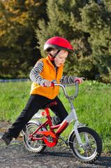 Cute young boy riding his bike