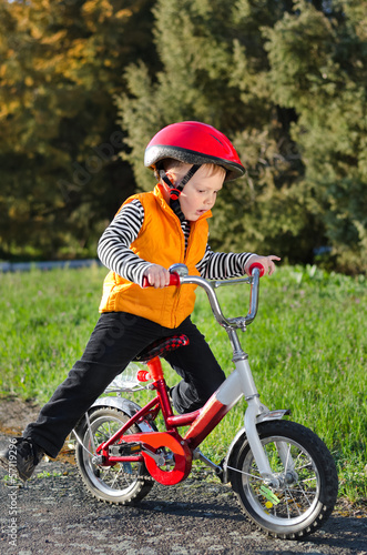 Cute young boy riding his bike