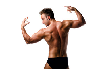 Attractive young muscular man naked posing, seen from the back
