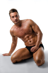 Attractive young muscular man posing on his knees