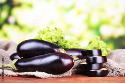 Fresh eggplants on table on bright background
