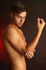 Young man with hand pain on dark background