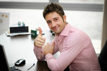 Cheerful office worker at desk doing thumb up sign and smiling