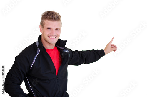 Smiling, young personal trainer pointing finger at blank space