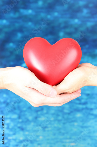 Heart in hands on blue background