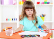 Little girl draws sitting at table in room on shelves