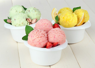 Tasty ice cream scoops in bowls, on wooden table