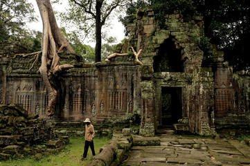 angkor - prheah khan temple, man walks through the ruins