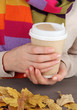 Hot drink in paper cup in hands with wooden table close up