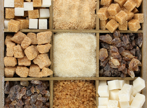 Different types of sugar in wooden box close-up