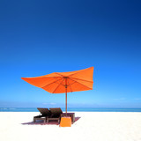 Beach with orange sun umbrella