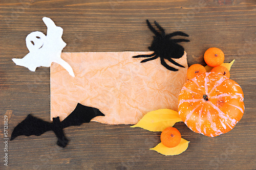 Old paper with Halloween decorations on grey wooden background
