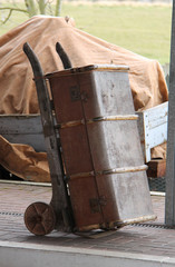 A Luggage Trolley with Trunk at a Railway Station.