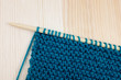 Garter stitch in teal yarn on knitting needle