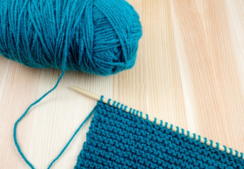 Ball of blue wool with knitting on the needle