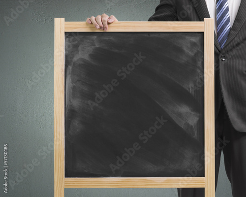Businessman hold dirty wooden chalk board in concrete background