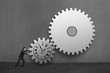 Businessman rolling large concrete gears with clock drawing in c
