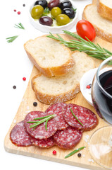 antipasto - salami, bread, olives and glass of wine isolated