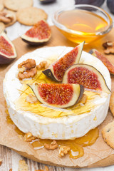 Camembert cheese with honey, figs and walnuts on a wooden board