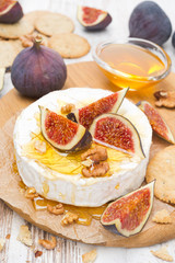 Camembert cheese with honey, figs, walnuts and crackers