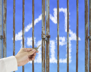 Hand hold key unlocking locked door with cloud house in blue sky