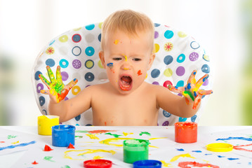 happy child draws with colored paints hands