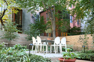 Garden furniture on patio behind New York City brownstone