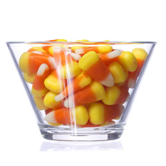 Halloween candy corn in glass bowl isolated. Closeup