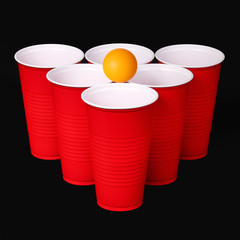 Beer pong. Red plastic cups and orange tennise ball over black
