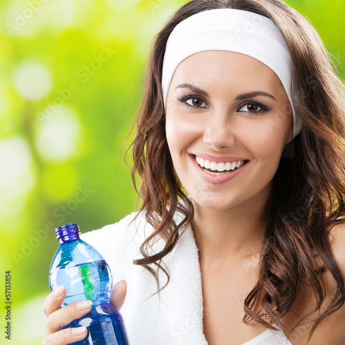 Woman with bottle of water, outdoors