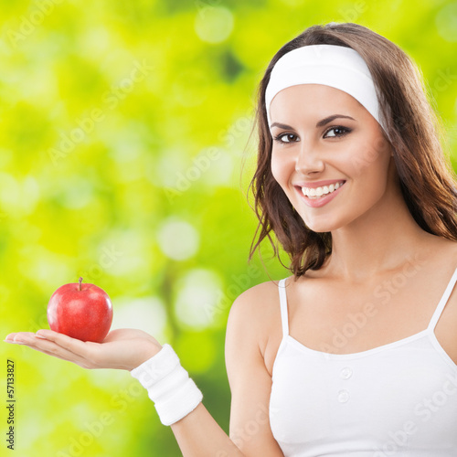Woman in fitness wear with apple, outdoors