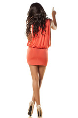 pretty girl in orange dress pointing a finger in the blank