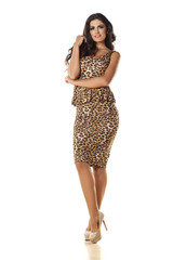 pretty girl posing in a leopard print dress on white