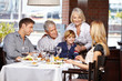 Glückliche Familie sitzt im Restaurant - 57135073