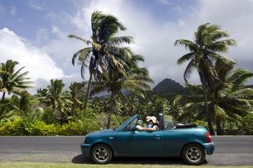 Couple traveling by convertible car in a Pacific Island