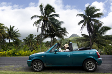 Young woman traveling by convertible car in a Pacific Island
