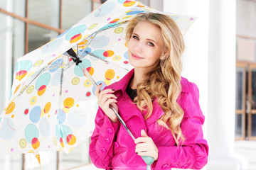 girl with umbrella in pink raincoat