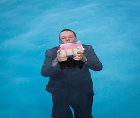 Senior man holding piggy bank above water