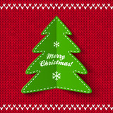 Green Christmas tree on red knitted background