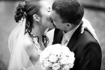 Closeup portrait of bride and groom kissing outdoors